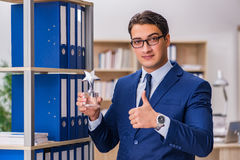 The young man standing next to the shelf with folders Stock Image