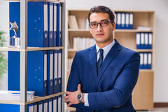 The young man standing next to the shelf with folders Stock Photo