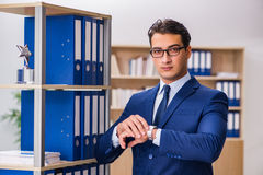 The young man standing next to the shelf with folders Royalty Free Stock Photography