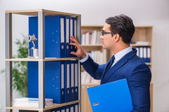 The young man standing next to the shelf with folders Stock Photos