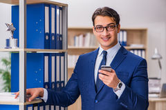 The young man standing next to the shelf with folders Royalty Free Stock Images