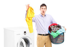Young man standing next to a washing machine  Stock Images
