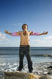 Young Man Standing on Ocean Rock with Arms Outstre. A tattooed young man standing on a rock in the ocean. He is looking up to the sky, and his arms are Stock Photos
