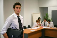 Young man standing at the office. Portrait of a young man with a briefcase standing at the office Stock Photography
