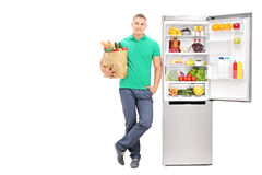 Young man standing by an open refrigerator Stock Photo