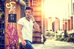 Young man standing outdoors on cellphone. Handsome young man standing outdoors in urban environment on metal stairs, talking on cell phone royalty free stock photos