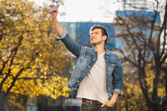 Young man standing outdoors holding mobile phone Stock Images