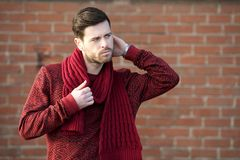 Young man standing outdoors with sweater and scarf Royalty Free Stock Photos