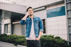 Young man standing outdoors, talking on the phone. royalty free stock image