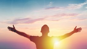 Young man standing outstretched at sunset. Victory stock photos
