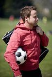 A young man standing in the park, carrying a football and a sports bag Royalty Free Stock Photography