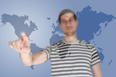 Young man standing and pointing on the map. Casual young man touching world map screen Royalty Free Stock Photography