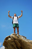Young man with standing with raised hands on top of a mountain. Winnerer and sucsess concept. Stock Image