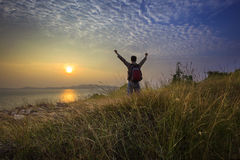 Young man standing and rising hand as victory on grass hill looking to sun above sea horizontal with dramatic colorful sky. Background royalty free stock image