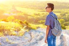 A young man standing on the road with a backpack looking away at the sun stock image