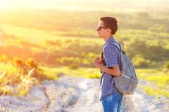 A young man standing on the road with a backpack looking away at the sun stock photos