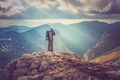 Young man standing on a rock and looking at a beautiful mountain Royalty Free Stock Image