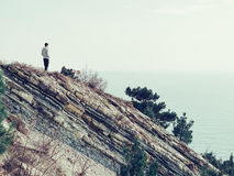Young man standing on a rock outdoor Stock Image