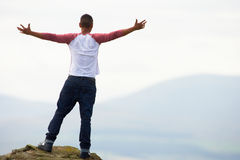 Young Man Standing On Rock With Outstretched Arms Stock Photos