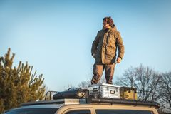 Man standing on top of a van. Young man standing on the roof rack of a van next to boxes and gear. He is looking sideways while the sun is casting a warm low royalty free stock photo