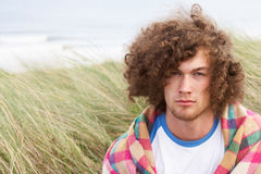 Young Man Standing In Sand Dunes. Wrapped In Blanket Stock Photos