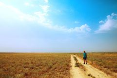 Young man standing on the road in savannah. Heat, sun, blue sky. dry ground. Young man standing in the savannah. Heat, sun, blue sky. dry ground royalty free stock photo