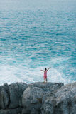 Young man standing on the sea-cliff  with his arm in the air and enjoy the view Royalty Free Stock Images