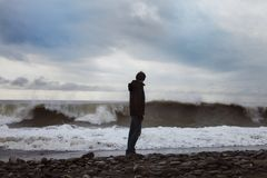 Young man standing on the sea shore. A young man standing on the sea shore Royalty Free Stock Images