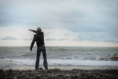 Young man standing on the sea shore Stock Photography