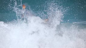 Young man standing in sea by waist-high give big thumb up knocking down by wave stock video