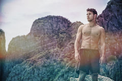 Young man standing shirtless, hills in background Royalty Free Stock Photo