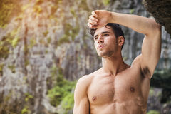 Young man standing shirtless, hills in background Stock Photo