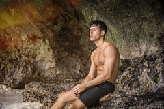 Young man standing shirtless, hills in background Royalty Free Stock Photos