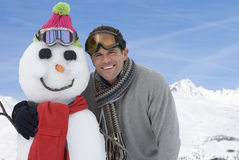 Young man standing by snowman, smiling, portrait Stock Photo