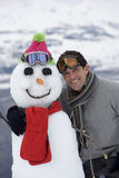 Young man standing by snowman, smiling, portrait Royalty Free Stock Image