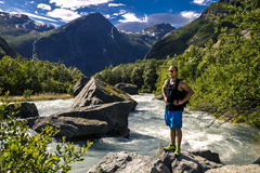Young man standing on the stone next to the river, Norway. Young and attractive man in blue shorts is standing on the rocks on the mountain river on sunny day Stock Photography
