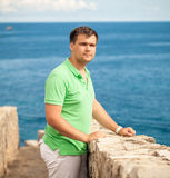 Young man standing on stone wall at seaside fortress Royalty Free Stock Photos