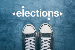 Young man standing on the street, elections sign on road Royalty Free Stock Image