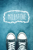 Young man standing on the street, milestone marking on road Stock Image