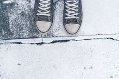 Young man standing on the street. Top view of worn gray sneakers on concrete floor with crack line as border - concept of obstacles, difficulties, hardship and Stock Images