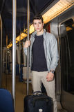 Young man standing in subway train going on vacation Stock Image
