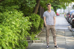 Young man standing on the summer street. Royalty Free Stock Photos