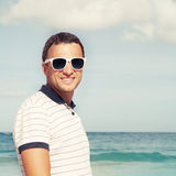Young man standing with sunglasses on sea coast Royalty Free Stock Images