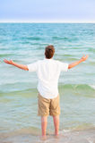 Young man standing in surf with arms up Stock Photos