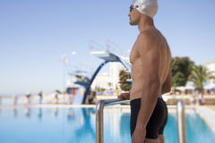A young man standing by a swimming pool Stock Images