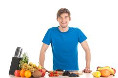 Young man standing at table with fruits. Stock Photography