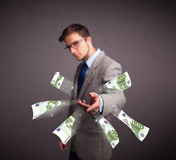 Young man standing and throwing money Stock Photos