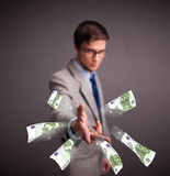Young man standing and throwing money Stock Photography