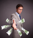 Young man standing and throwing money Stock Images