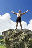 Young man standing on top of a cliff with arms raised. Beautiful mountain landscape Royalty Free Stock Photography